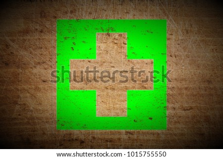 grungy medical cross sign painted on scratched wooden board texture background