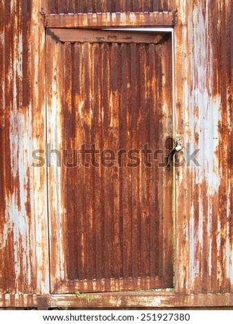 grungy metal surface and lock on rusty iron door - stock photo