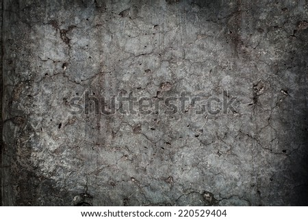 Grungy monotone stone wall with many fractures and cracks. - stock photo