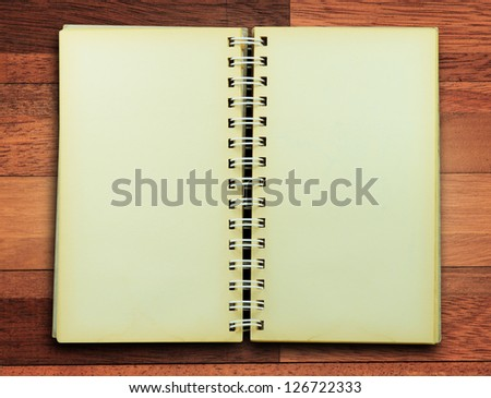 Grungy notebook on wood background.