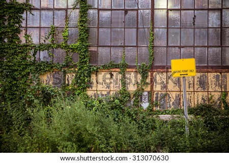 Grungy old industrial exterior with windows and overgrown vines and weeds - stock photo