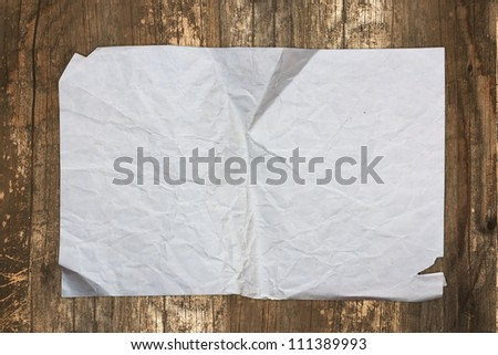 Grungy paper sheet on a wooden background