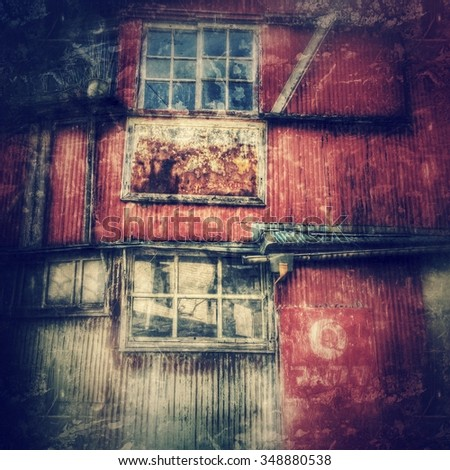 Grungy, rusting windows and corrugated metal wall of an old, abandoned, decrepit house doubling as a shop, with vignette and grunge texture overlay - stock photo