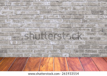 Grungy textured grey brick and stone wall with warm brown wooden floor inside old neglected and deserted interior, masonry and carpentry brickwork concept - stock photo