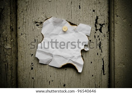 Grungy torn note paper nailed on rustic old weathered background.