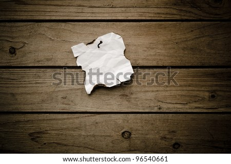 Grungy torn note paper nailed on wood background. - stock photo