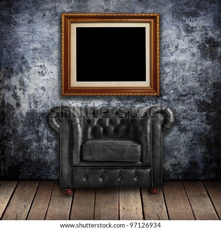 Grungy wall with Classic Brown leather armchair and gold frames background. - stock photo