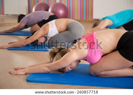Gruop of people stretching spine during yoga clasess - stock photo