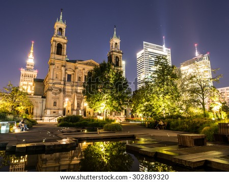 Grzybowski Square with All Saints' Church and Palace of Culture and Science (PKiN) and skyscrapers behind it in the downtown of Warsaw, illuminated by night. - stock photo