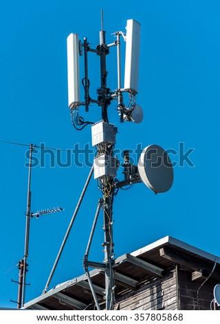 GSM radio satellite antenna on a mountain house cottage in the alps - stock photo