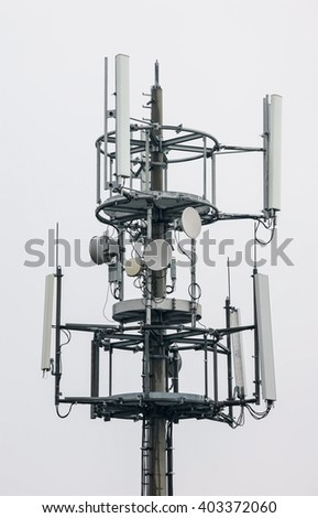 GSM tower, top of the multiderictional antenna tower - transmitter - with some small communication dishes. - stock photo