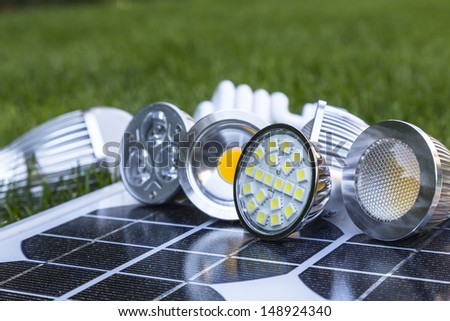 GU10 LED bulbs on photovoltaics, in the grass E27 LED and CFL - stock photo