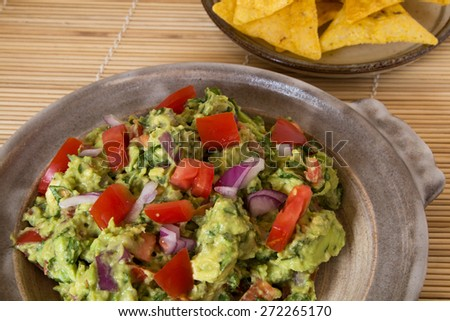 Guacamole and corn chips served in a pottery dish on a bamboo mat  - stock photo