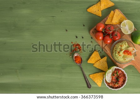 guacamole and salsa with tortilla chips on wooden background - stock photo