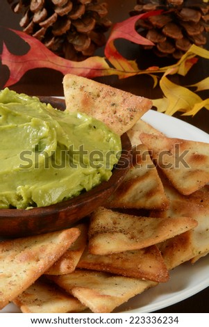 Guacamole and toasted pita chips on a holiday table