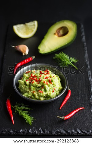 Guacamole dip and ingredients on black background, selective focus - stock photo