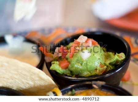 Guacamole dip in a small black dish. - stock photo