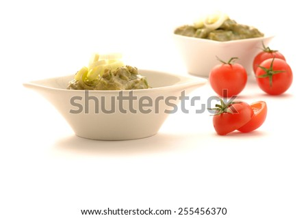 guacamole dip in bowl isolated on white background and tomato slice - stock photo