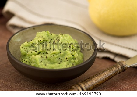 Guacamole in bowl on wooden table  - stock photo
