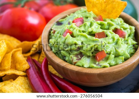 Guacamole in Wooden Bowl with Tortilla Chips and Ingredients - stock photo