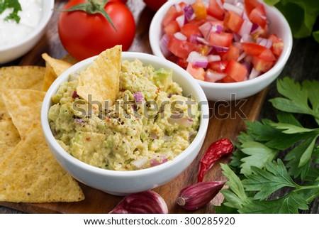 guacamole sauce, tomato salsa and corn chips, top view, closeup - stock photo