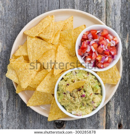 guacamole, tomato salsa and corn chips on a plate, top view, closeup - stock photo