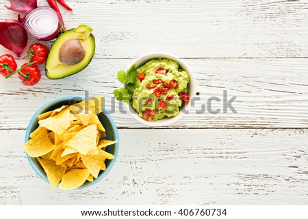 Guacamole with avocado and tomatoes mexican food. white wooden background - stock photo