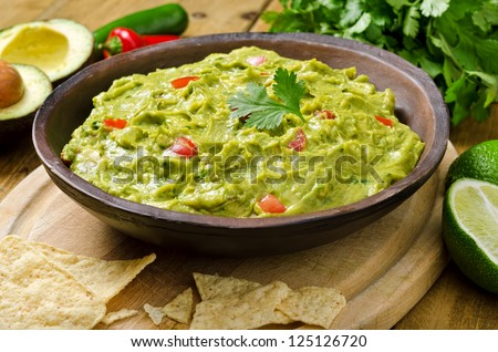 Guacamole with avocado, lime, tomato, and cilantro with tortilla chips. - stock photo