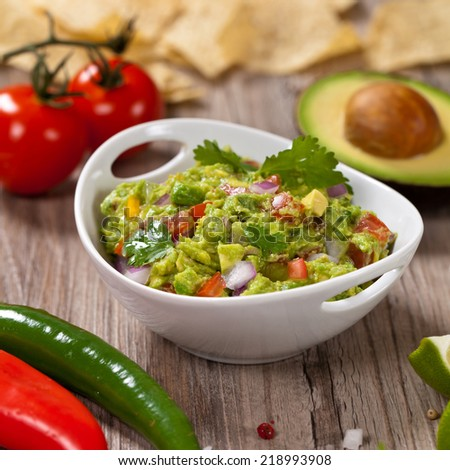 Guacamole with avocado, lime, tomato and cilantro with tortilla chips - stock photo