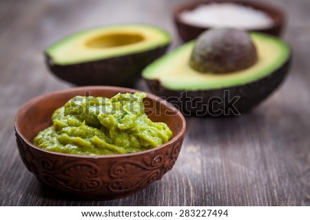 Guacamole with avocado on wooden table
