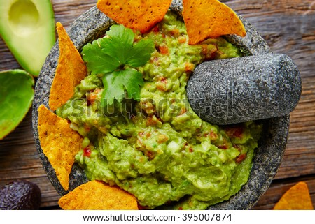 Guacamole with nachos avocado in Mexican molcajete in aged wood table - stock photo