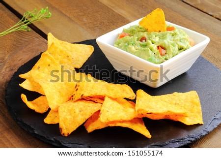 Guacamole with tortilla chips or nachos - stock photo