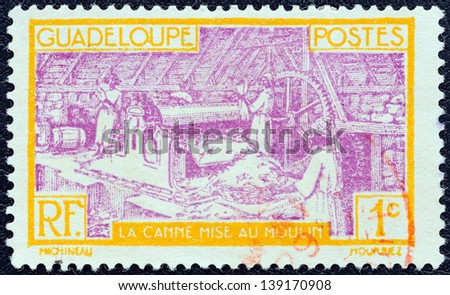 GUADELOUPE - CIRCA 1928: A stamp printed in France shows Sugar Refinery, circa 1928. - stock photo