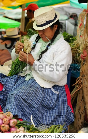 GUALACEO, ECUADOR - AUGUST 22: Ecuadorian ethnic women in national clothes selling agricultural products and other food items on a market in the Gualaceo village on August 22, 2012 in Gualaceo