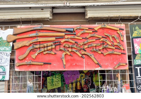 GUANAJUATO, MEXICO - NOVEMBER 9, 2013: Rifles and pistols decorated in the store front of souvenir shop in the historic UNESCO Heritage Site of Guanajuato.
