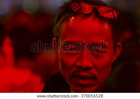 GUANGZHOU, CHINA - JAN. 31. 2016:Man waits for his train in front of illuminated arrival-departure board on main railway station , as travel for the annual Spring Festival holidays continues - stock photo