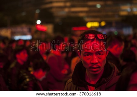 GUANGZHOU, CHINA - JAN. 31. 2016:Man waits for his train in front of illuminated arrival-departure board on main railway station in Guangzhou, travel for the annual Spring Festival holidays - stock photo