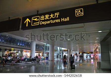 GUANGZHOU, CHINA-JUNE 22: Departure hall sign board in Guangzhou Baiyun International Airport on June 22, 2013. Guangzhou is the third largest city in China. - stock photo