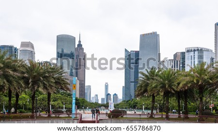 GUANGZHOU, CHINA - MARCH 31, 2017: tourists on square in Zhujiang New Town of Guangzhou city in spring rainy day. Guangzhou is the third most-populous city in China with population about 13,5 mln