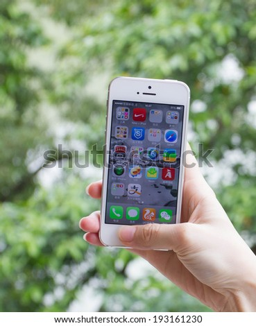 GuangZhou, China - May 2, 2014: Female hands holding a iphone5. iPhone 5 is a smartphone developed by Apple Inc. It is part of the iPhone line. iPhone is world favorite smartphone.  - stock photo