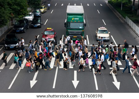 GUANGZHOU, CHINA  - MAY 2: Group of people crossing the street-upper view on May 2, 2013 in Guangzhou. China is the world's most populous country,Population over 1.3 billion. - stock photo