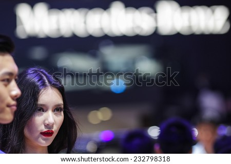 GUANGZHOU, CHINA - NOV. 20. 2014: Girl posing for spectators by the Mercedes-Benz car on the 12th China International Automobile Exhibition in Guangzhou, Guangdong province. - stock photo