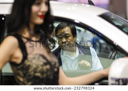 GUANGZHOU, CHINA - NOV. 21. 2014: Man looking in Cadillac Escalade car on the 12th China International Automobile Exhibition in Guangzhou, Guangdong province. - stock photo