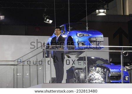 GUANGZHOU, CHINA - NOV. 20. 2014: Man on the Subaru stand standing in front of car model cuted in half on the 12th China International Automobile Exhibition in Guangzhou, Guangdong province. - stock photo