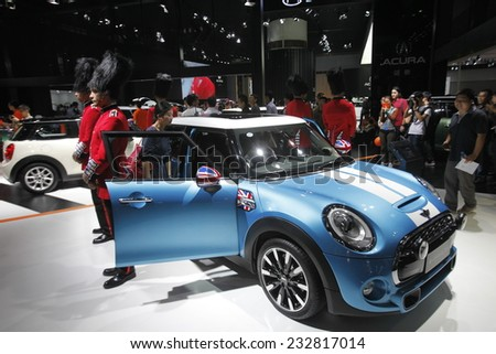 GUANGZHOU, CHINA - NOV. 22. 2014: Models wear costumes resembling Buckingham Palace guards stand around a Mini Cooper during the 12th China International Automobile Exhibition. - stock photo