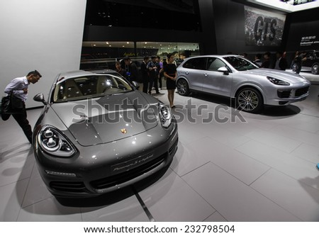 GUANGZHOU, CHINA - NOV. 20. 2014: People observing new Porsche Cayenne e-hybrid and Panamera e-hybrid vehicles on the 12th China International Automobile Exhibition in Guangzhou, Guangdong province. - stock photo