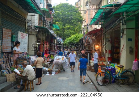 GUANGZHOU, CHINA, OCTOBER 1, 2013: People are passing by through minor street on Guangzhou, where they are shopping products needed for daily life.
