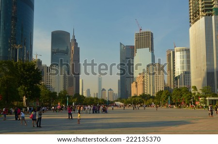 GUANGZHOU, CHINA, OCTOBER 2, 2013: People are passing by through the main shopping boulevard leading from the pearl river to tianhe in guangzhou, which is surrounded by tall skyscrapers. - stock photo
