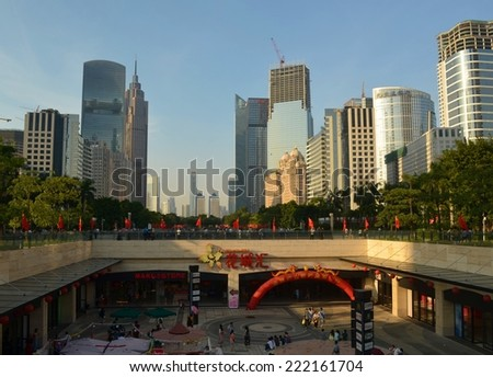 GUANGZHOU, CHINA, OCTOBER 2, 2013: People are passing by through the main shopping boulevard leading from the pearl river to tianhe in guangzhou, which is surrounded by tall skyscrapers.