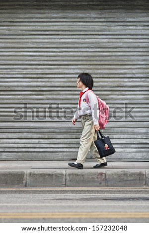 GUANGZHOU-JAN. 9. Ten years old Zhou Su walks back home. Since 1979, China has a one-child policy. Most families allowed have only one child, or risk steep government fines. Guangzhou, Jan. 9, 2008. - stock photo